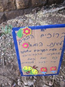 """A homemade sign erected in the new garden reads: """"Welcome to the pretty garden of the cute children of our neighborhood who put a lot of brains and brawn into it so that G-d Willing it will grow and bloom"""""""
